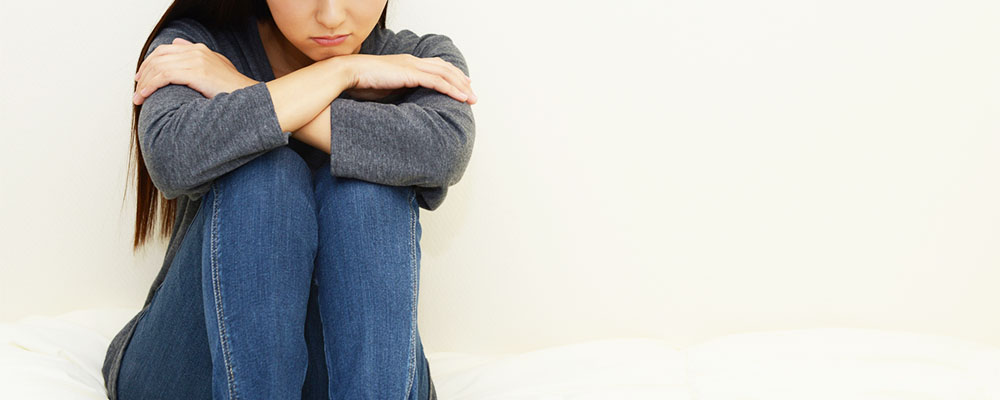 ベッドの上で膝を抱える女性